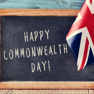 a chalkboard with the text happy commonwealth day written in it and the Union Flag, on a wooden surface, against a blue rustic wooden background