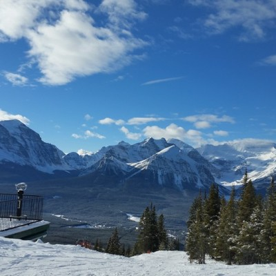 A person looking out from a viewpoint at a view of snow-capped mountains in Banff, Canada