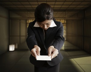 Japanese businesswoman bowing slightly whilst offering her business card - the ritual of the 'Meishi'