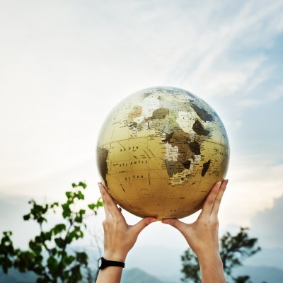 World Global Networking International Society Concept - a pair of hands holding a globe with a blue sky backdrop