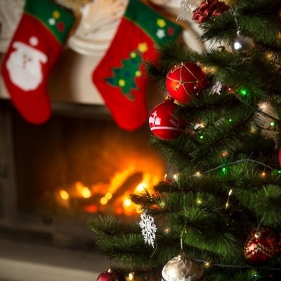 Beautiful background of Christmas tree at living room with burning fireplace decorated with traditional stockings for gifts
