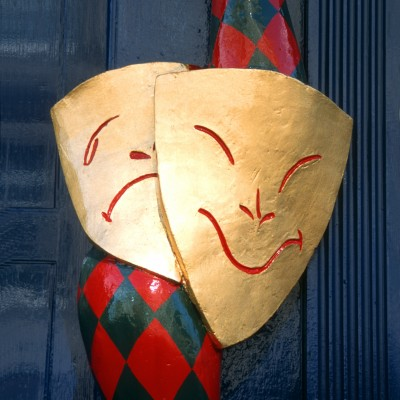 """Edinburgh, Scotland, UK - October 10, 2006: Decoration outside the information office of the Fringe Festival of Edinburgh, with modern mask """"smile-sad"""" as symbol of theater."""
