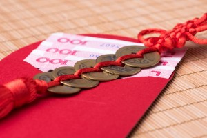 Close-up of decorative Chinese lucky coins and lucky money in red envelope on bamboo mat, selective focus