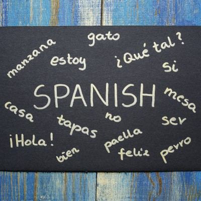 concept of learning spanish language, words written on black paper card on wooden background