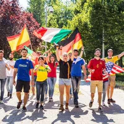 Happy supporters from different countries walking and chanting together. Fans from England, USA, Brazil, Spain, Portugal and other countries enjoying sport together. Respect and fair play concepts