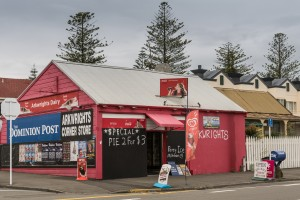 Napier, New Zealand - March 9, 2017: Arkwrights Dairy is a corner store selling groceries, newspapers and basic household products. Red paint, colored advertisement, cloudy sky and neighborhood street scene.