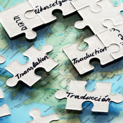 puzzle pieces placed on world map ,reffering to different languages and translation