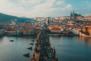 View of lots of people walking on Charles Bridge against a backdrop of buildings in Prague