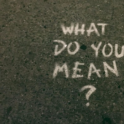 The phrase 'what do you mean?' written in white chalk on the ground
