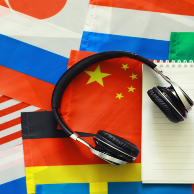 Pair of headphones with flags and a notebook in the background