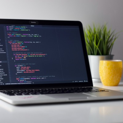 A picture with coding on a computer screen, on a desk, with a cup and a plant in the background