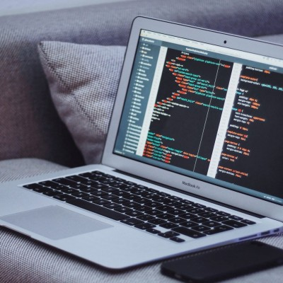 Picture of a laptop on the arm of a sofa with coding on the screen