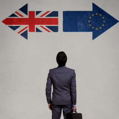 A picture of a man holding a brief case looking at two arrows on the wall, one with the EU flag pointing left, and one with the UK flag pointing right